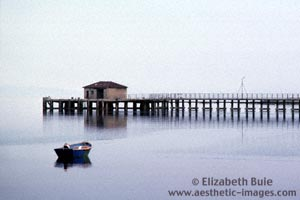 Small boat and pier in tranquil bay © Elizabeth Buie