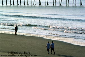 Early-morning walkers and prospector on the shore, Ocean Isle Beach, North Carolina (copyright Elizabeth Buie)